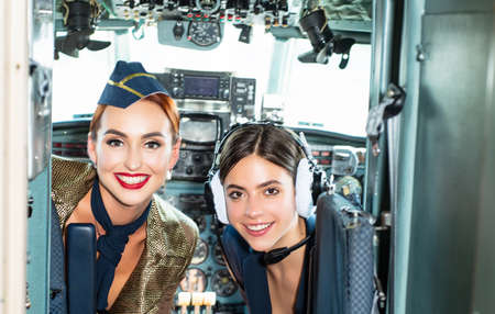 Girls looking at camera. Happy and successful flight. Back view from the inside of the plane. Women pilots smile and wish a successful flight. Looking at camera in plane.