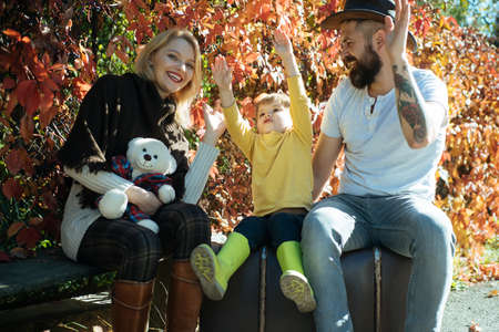 Happy family together. Blonde mom and bearded dad teach baby to be joyous, to celebrate victory. Emotional intelligence. Indian Summer. Warm days in autumn. Weekends without kindergarten.