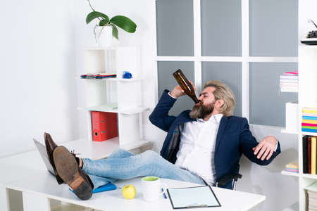 Tired bored businessman yawning at workplace near laptop, boring work, dead end job, overwork extra after hours, drink alcohol. Foto de archivo