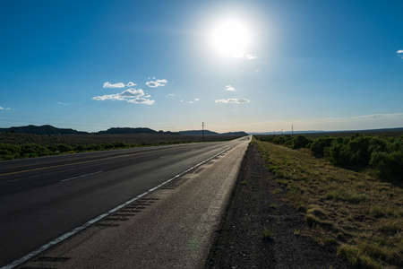 Classic panorama view of an endless straight road running through the barren scenery of the American Southwest.