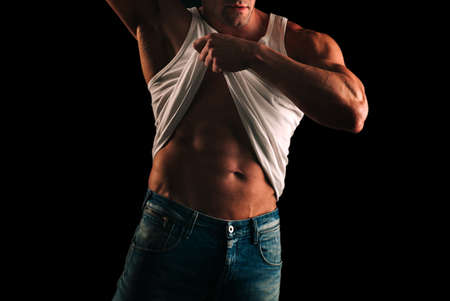 Naked man. Handsome shirtless muscular man standing in studio, isolated on black. Reklamní fotografie