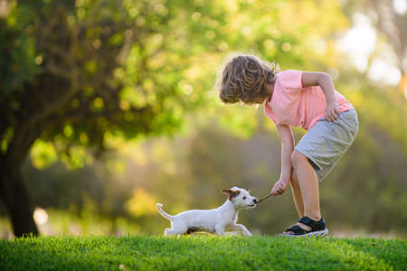 Kid with pets puppy. Happy child and dog hugs her with tenderness smiling.