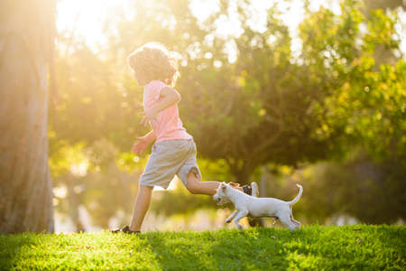 Boy child walk with puppy. Kid with pets running. Happy Child and dog runs at backyard lawn. Banque d'images