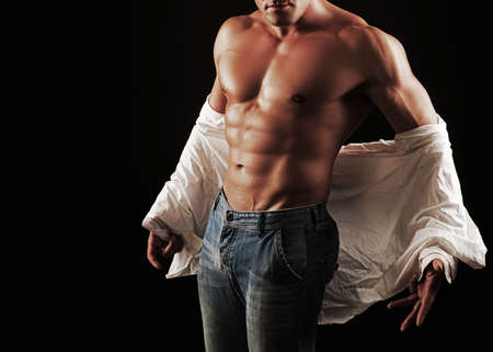 Handsome muscular young man taking off shirt. Sexy torso of a muscular man. Фото со стока