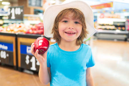 Cute toddler boy in a food store or a supermarket choosing fresh organic apple. Healthy lifestyle for young family with kids. Sale, consumerism and kids concept.