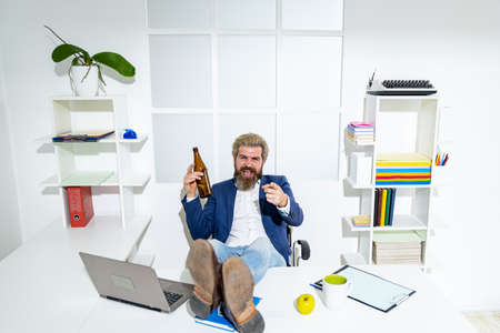 Tired bored businessman yawning at workplace near laptop, boring work, dead end job, overwork extra after hours, drink alcohol. Drunk office worker. Foto de archivo