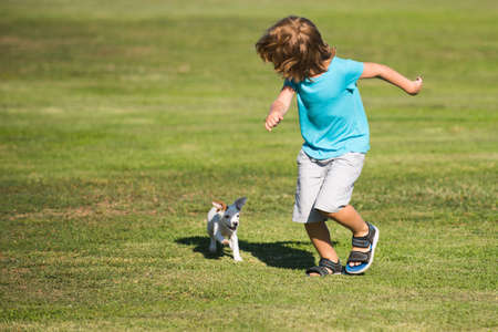 Happy child boy run with a dog outdoor.