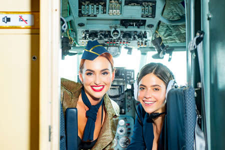 Beautiful woman pilot wearing uniform. Happy and successful flight. Looking at camera in plane. Girls looking at camera. Two Women Pilots Sitting in Cabin of Modern Aircraft. Imagens