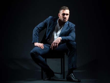 Portrait of business man dressed in a blue suit posing on black studio. Standard-Bild