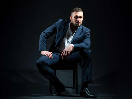 Portrait of business man dressed in a blue suit posing on black studio. Stock Photo