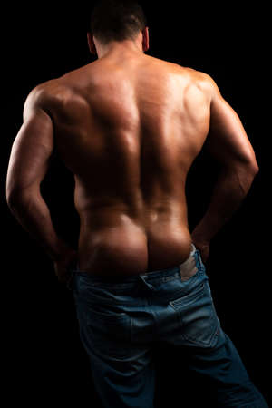 Sexy portrait of young hot guy. Muscular man. Male madel with torso. Hunk with athletic body. Sensual buttocks.