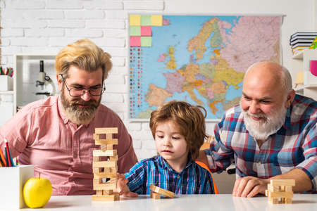 Head shot portrait smiling grandfather, father and preschool son looking at camera. Jenga game at home.