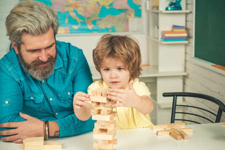 Child play concept. Children building wood blocks at home. Father and son playing stacking wood blocks   games for meditation practice. Hand movement control Building Computational Skills. Reklamní fotografie