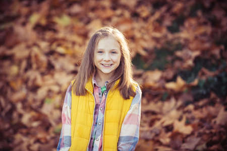 Adorable little girl in the beauty park. Outdoor. Autumn outdoor portrait of beautiful happy child girl walking in park or forest. Adorable little girl in the park.