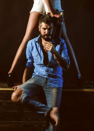 Handsome bearded man holding a glass of red wine. Sexy long fit woman legs. Bearded man wearing total jeans look. Loving couple playing sexual games. Lovers foreplay concept. Banco de Imagens