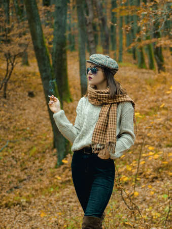 Autumnal melancholy. Autumn is here. Pretty woman in hat and sunglasses smoking cigarette forest background. Fall fashion accessory. Enjoy fall season. Relaxing smoking. Woman enjoy smoking alone