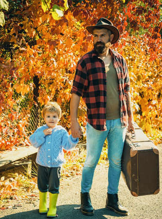 Telling stories about past times. Father with suitcase and his son. Bearded dad telling son about travelling. Traveler with lot experience. Spirit of adventurism. Family time. Adventure with son