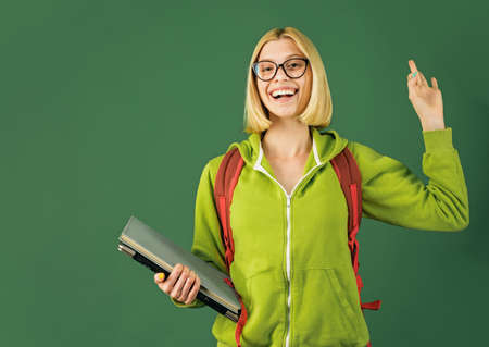 Portrait of creative young smiling female Student in glasses. Smiling girl student or woman teacher portrait on green wall blackboard background. Thank You Teacher. 免版税图像