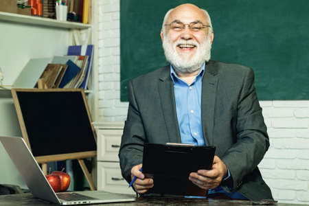 Portrait of male University Teacher indoors. Knowledge day. Teacher and tutoring education concept. Professor in class on blackboard background. Bearded professor at school lesson in classroom. 免版税图像