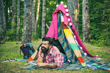 Active people. Handsome bearded man inside camping tent. Cozy play tent for man. Hut of branches. Rest camping.