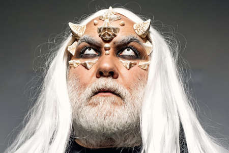 Bearded old man dressed like Halloween monster. Wizard demon man with dragon skin and horns. Man evil with horns. Alien with dragon skin and grey beard. Devil horns.
