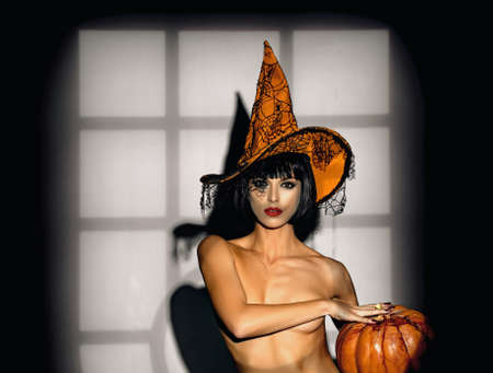 Night time halloween party for adult. Sexy stripper Woman with pumpkins. Halloween lingerie model. Standard-Bild