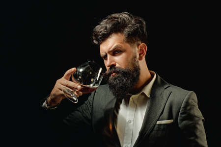 Alcohol concept. Stylish elegant bearded man Bartender holds cognac glass. Man or businessman drinks cognac on black background. Foto de archivo