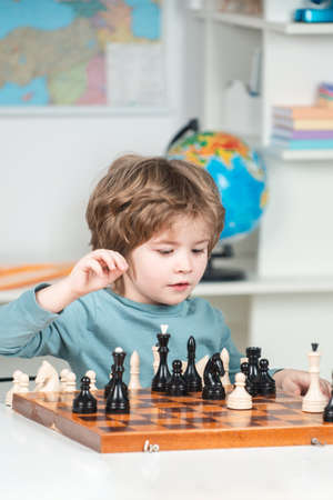 Boy kid playing chess at home. Chess school. Clever concentrated and thinking child while playing chess. Games and activities for children. Family concept. 免版税图像