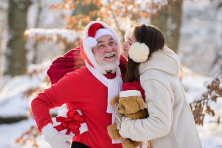 Mrs Santa giving Santa a thank you kiss for Christmas present on snowy forest. Funny Santa with Gift on Christmas Eve outside.