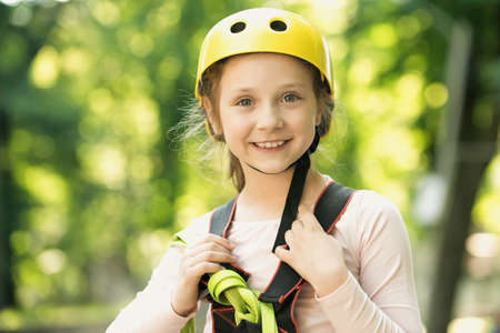 Go Ape Adventure. Happy Little girl climbing on a rope playground outdoor. Little girl concept. High ropes walk. Early childhood development. Children fun.