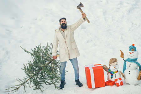 Hipster woodsman with Christmas tree. Man is going to cut a Christmas tree. Christmas tree cut. Bearded Man cutting Christmas tree. Standard-Bild