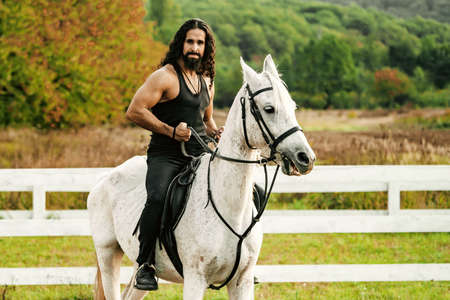 Rider on gray arabian horse in the field. Handsome bearded man riding horse at farm. Beautiful horse with man rider trotting on autumnal field. Equestrian and animal love concept.