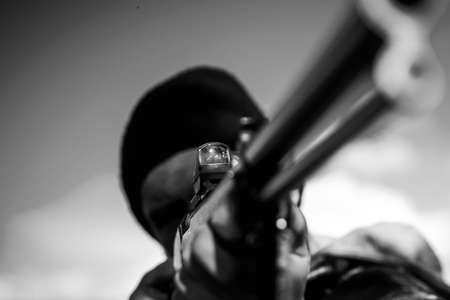 Hunter aiming rifle in forest. Hunter with shotgun gun on hunt. Autumn hunting season. Barrel of a gun. Hunting gun. Stock Photo