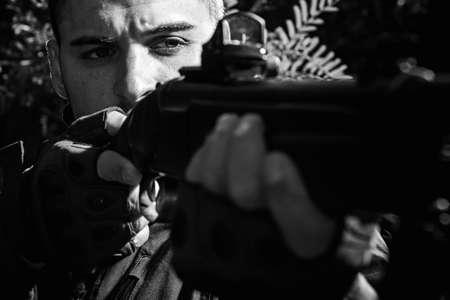 Hunter with shotgun gun on hunt. Hunter Target with laser sight. Collimating sight. Pulled the trigger of the shotgun. Close up Portrait of hamdsome Hunter. Stock fotó