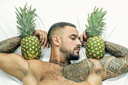 muscular man hold pineapple fruit on biceps. brutal sportsman relax in bed. steroids. sexy ab of tattoo man diet. male health. muscular macho man with athletic body. exotic fruit healthy food vitamin.