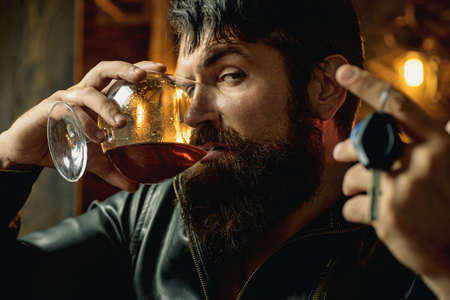 Man with beard holds glass brandy. Macho drinking. Confident man with car keys in his hand. Do not drive drunk. Stop drinking.
