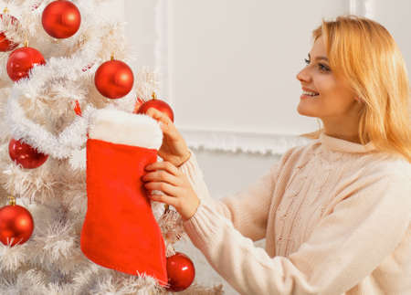 White christmas tree red balls. Christmas stockings. Home Christmas atmosphere. Winter holidays and people concept.