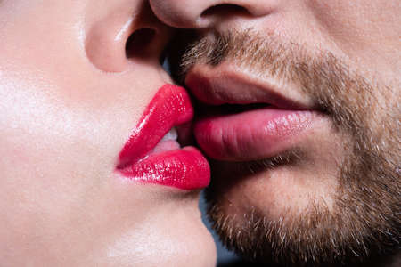 Close-up of young romantic couple is kissing each other. Red lips and sensual open mouth.