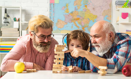 Happy man family concept laugh and have fun together. Grandfather watching son and grandson playing board game at home.