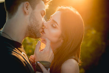 Sexy lovers kiss outdoor at sunset. Sensual Young people.