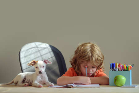 cute little student with pet puppy dog writing to notebook at home.