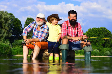 Grandson with father and grandfather fishing by lake. Father, son and grandfather on fishing trip. Family bonding. Anglers. Happy fisherman with fishing rod. Banco de Imagens