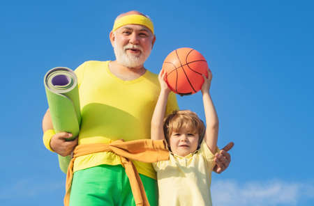 Summer sport and fun lifestyle. Sports education. Grandpa and grandson spotting. Father and child training together. I love sport. Banco de Imagens