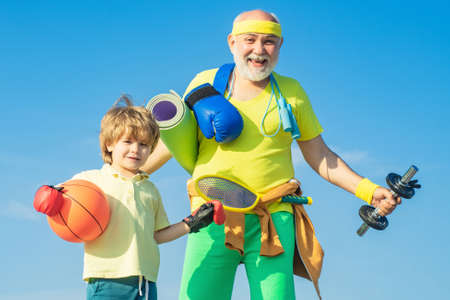 Sports for kids. Father and son sporting - family time together. Senior man and cute little boy exercising on blue sky background - isolated. Banco de Imagens