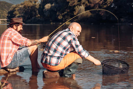 Young man and old mature man fly fishing. Man fishing and relaxing while enjoying hobby. Portrait of cheerful two bearded men fishing.