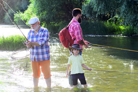 Grandfather and grandchild. Grandfather with son and grandson having fun in river. Summer day. Hobby and sport activity.