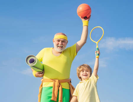 Grandfather and grandson with basketball ball and yoga mat in hands. Father and son having workout. Age is no excuse to slack on your health. Doing sports is free.