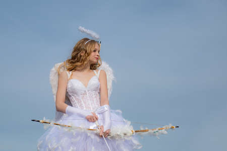 A child in the clothes of an angel on sky background. Little angel in love. Lovely girl cupid with bow and arrow is ready to find your love. Lovely child