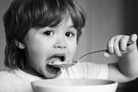 Hungry little boy eating. Cheerful baby child eats food itself with spoon. Tasty kids breakfast. Baby eating food on kitchen. Happy baby boy eats healthy food spoon itself.