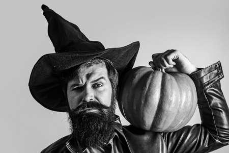 Trick or treat. Happy Halloween Stickers. Thanksgiving day cooking. Celebrating happy Thanksgiving day. Handsome man in Halloween hat holding pumpkin - portrait close up. Standard-Bild